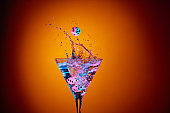 Dice fall in a glass of martini. Colourful cocktail in glass with splash.