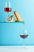 Blue cheese with bread, wine and rosemary on a blue background.