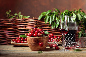 Cherry liquor and red cherries in a wooden bowl on a wooden table in garden.