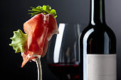 Prosciutto with rosemary and red wine on a dark background.
