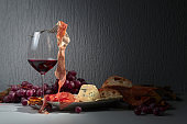 Glass of red wine with prosciutto and blue cheese.
