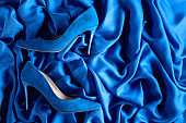 Blue women's corduroy shoes on a silk background.