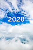 Sky cloud year 2020. Happy New year concept. 2020 cloud against the blue sky.Year 2020 symbol inscription on a background of blue sky from white smoke of clouds lit by a bright sun