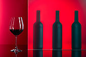 Bottles and glass of red wine on a red background.