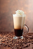 Glass cup with coffee and coffee beans on a brown background.
