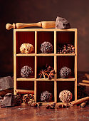 Chocolate truffles with broken pieces of chocolate and spices in wooden box.