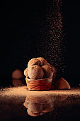 Chocolate truffles in small wooden dish sprinkled with cocoa powder. Black reflective background.