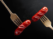 Grilled sausages on a forks.