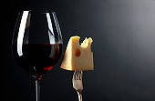Maasdam cheese with red wine on a black background.
