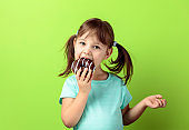 Four-year-old girl eat donut.