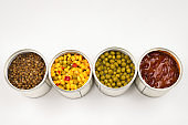 Canned food on white background. Green pea, beans, corn, lentils.