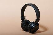 Black headphones on beige color background