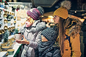 Family buying handmade cups on Christmas market