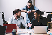 Positive male colleagues having fun during teamwork on design project sitting at table with laptops in modern office.Cheerful friends laughing during break working together in finance company