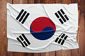 Flag of South Korea on a wooden table background. Wrinkled South Korean flag top view.