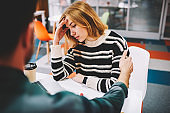 Male employeer talking with female colleague about bad news of unsuccessful project sitting at desktop in office.Worried blonde student feeling stress during working process at laptop computer