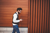 Trendy male blogger walking on publicity area and installing media application on cellular phone, young stylish hipster guy dialing number on modern smartphone device during free time outdoors