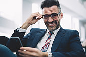 Half length portrait of happy successful businessman 50 years old making payment online on smartphone while smiling at camera.Positive proud ceo in formal wear with modern telephone in hands