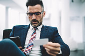 Confident mature executive manager in formal wear dialing phone number from business card on smartphone device.Serious entrepreneur 50 years old reading notification on modern telephone