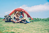 Hipster couple resting in tent camping on green grass during sunny summer day planning route,young woman pointing on map discussing direction for exploring nature with boyfriend on vacations