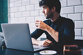 Handsome young man looking away while resting with cup of coffee in hand in cafeteria interior using modern laptop computer device connected to wireless 4G internet.Hipster guy sitting at netbook