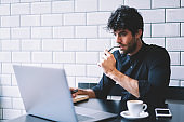Concentrated male graphic designer watching carefully online lesson on laptop computer connected to 4G internet.Pensive entrepreneur checking accounting database on netbook working in coffee shop