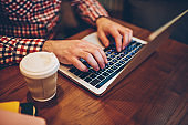 Cropped image of male hands typing information for website via keyboard on laptop computer connected to free wireless internet in coffee shop, it professional working remotely with modern netbook