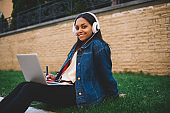 Portrait of smiling afro american student doing homework outdoors using laptop for research .Positive dark skinned hipster girl styling in university campus preparing for examinations outdoors