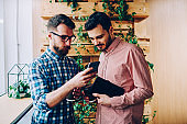 Young male friends checking new app for smartphones download files for installing, hipster guy having consultancy with colleague about booking on website showing him information on cellular