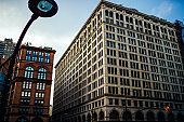 Old building exterior with windows of offices and corporate headquarters inside located in downtown, tall architecture construction with real estate for business and banks in megalopolis settings