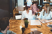 Group of young women joking with each other enjoying work break together sitting at table,positive crew of female and male employees spending free time with coffee and friendly communication