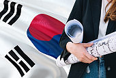 South Korean Architect woman holding blueprint against South Korea waving flag background. Construction and architecture concept.