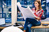 Positive female architect holding paper with blueprint satisfied with completed drafting before deadline, cheerful woman student staying overtime for drawing sketch checking planning sitting on window