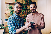 Half length portrait of cheerful hipster guys spending free time on hobby using vintage camera, smiling male students of courses checking equipment giving it to photography school coach enjoy learning
