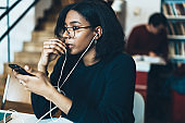 Pensive african american girl in eyewear listening music in earphone from smartphone playlist on free time, thoughtful female hipster enjoying music downloaded in app on mobile phone on leisure