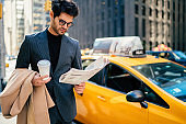Serious businessman concentrated on financial news from press standing on Manhattan near yellow cab,confident owner in elegant suit puzzled reading newspaper on street in downtown holding coffee to go