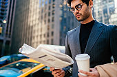 Pensive male in elegant outfit concentrated on information in daily newspaper holding coffee cup with copy space for brand name or logo,confident executive manager reading morning press on avenue