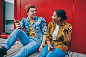 Cheerful multiracial male and female hipster guys in casual trendy wear discussing spending time together, happy couple in love laughing at jokes sitting outdoors with mobile phone. Real communication