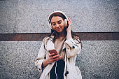 Attractive young hipster girl enjoying listening to music from playlist updating application on smartphone waiting for friends outdoors, female student blogging in social networks listening to radio
