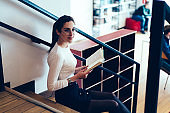 Portrait of pensive caucasian woman in eyewear sitting on stairs in college library with textbook for education, young brunette woman spending free time on literature hobby reading new best seller
