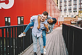 Joyful multiracial romantic couple in love spending weekends together having fun and laughing, cheerful people on dating, smiling boyfriends give his girlfriend ride on his back on city street