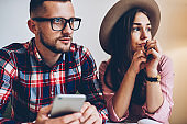 Young male and female colleagues thinking about problem solutions looking away while browsing in smartphone,handsome hipster guy sending message on cellular sitting in cafe interior with girlfriend