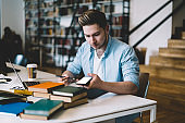 Pensive hipster guy using mobile phone sitting at desktop in college campus, serious millennial male updating application on smartphone with mock up screen connected to wireless internet in library
