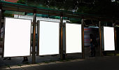 Bus station billboards with blank copy space posters for advertising text message or promotional content, empty mock up Lightbox for information, bus stop shelter clear display in urban city street