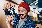 Happy smiling hipster guy in stylish apparel taking pictures of campus environment via vintage camera feeling prosperous from having good focus on obsolete lens, concept of photographing hobby