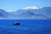 high mountains and tour boat on Mediterranean sea over clear sunny sky