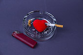 A smoking cigarette in a glass ashtray with a heart and a nearby cigarette lighter against a gray background