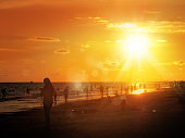 silhouetted people on public beach over orange colored sunset sky