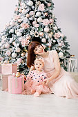 A beautiful mother with a small daughter in pink dresses playing around a decorated Christmas tree with gifts.