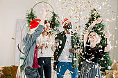 Group of four cheerful fashion dressed friends standing in front of Christmas decorations and celebrating New Year, drinking champagne